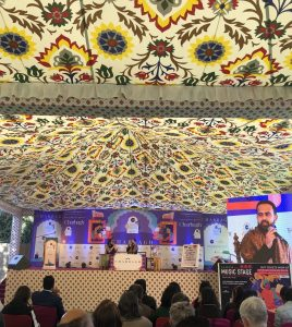 Author Varun Thomas Mathew shown on stage speaking with a panelist and also shown on a large screen, with flowered tent canopy overhead