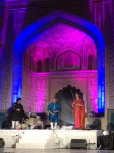 Brightly lit stage with two men and a woman in silk robes performing music