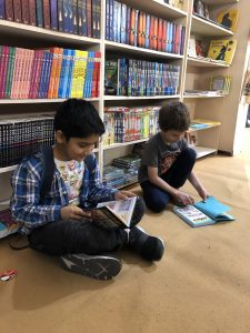 Two boys crouch on the floor reading Dog Man books