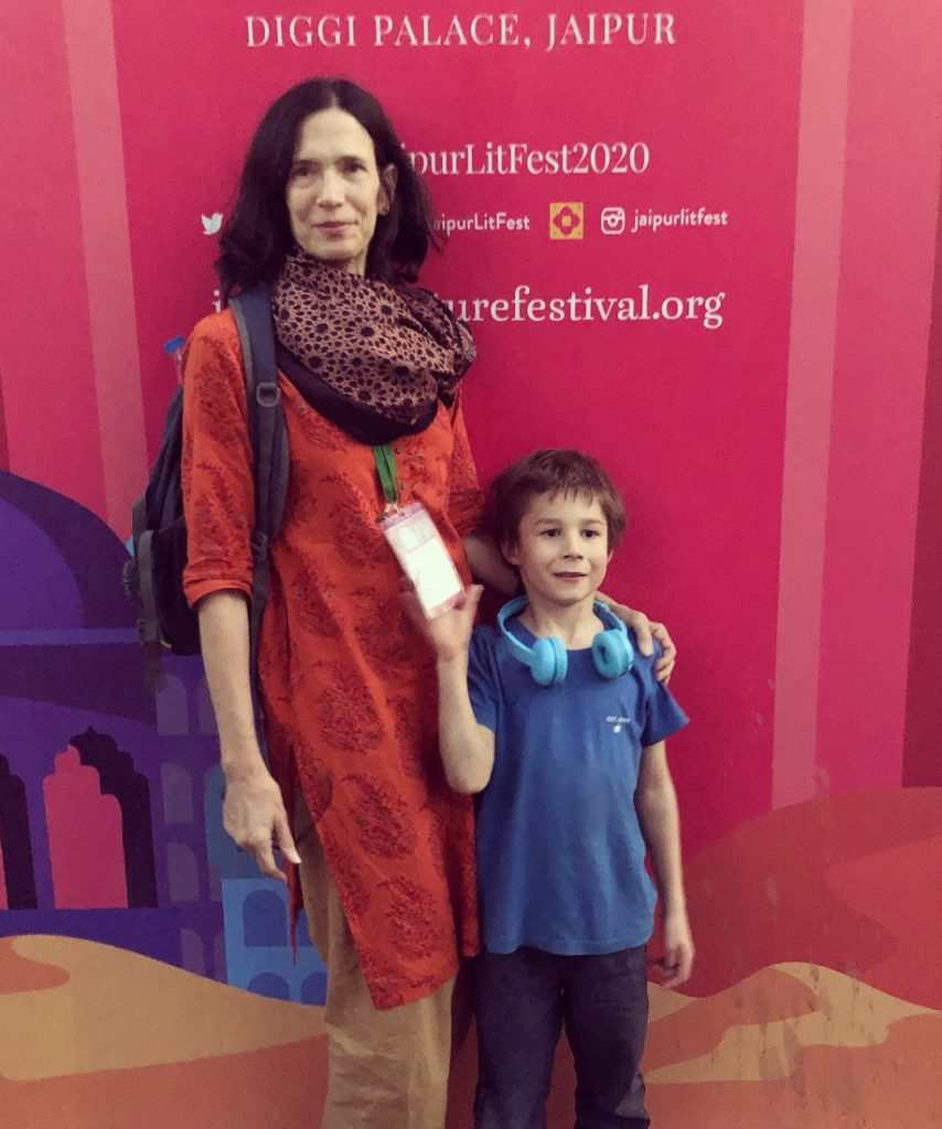 Elizabeth Kadetsky in front of a sign for the Jaipur Literature Festival, wearing her press badge and standing with her young son, Alexander.
