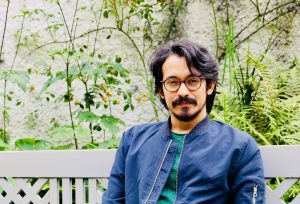 NER Poet Rohan Chhetri sits on a white bench with beard, blue jacket, and yellow flowers