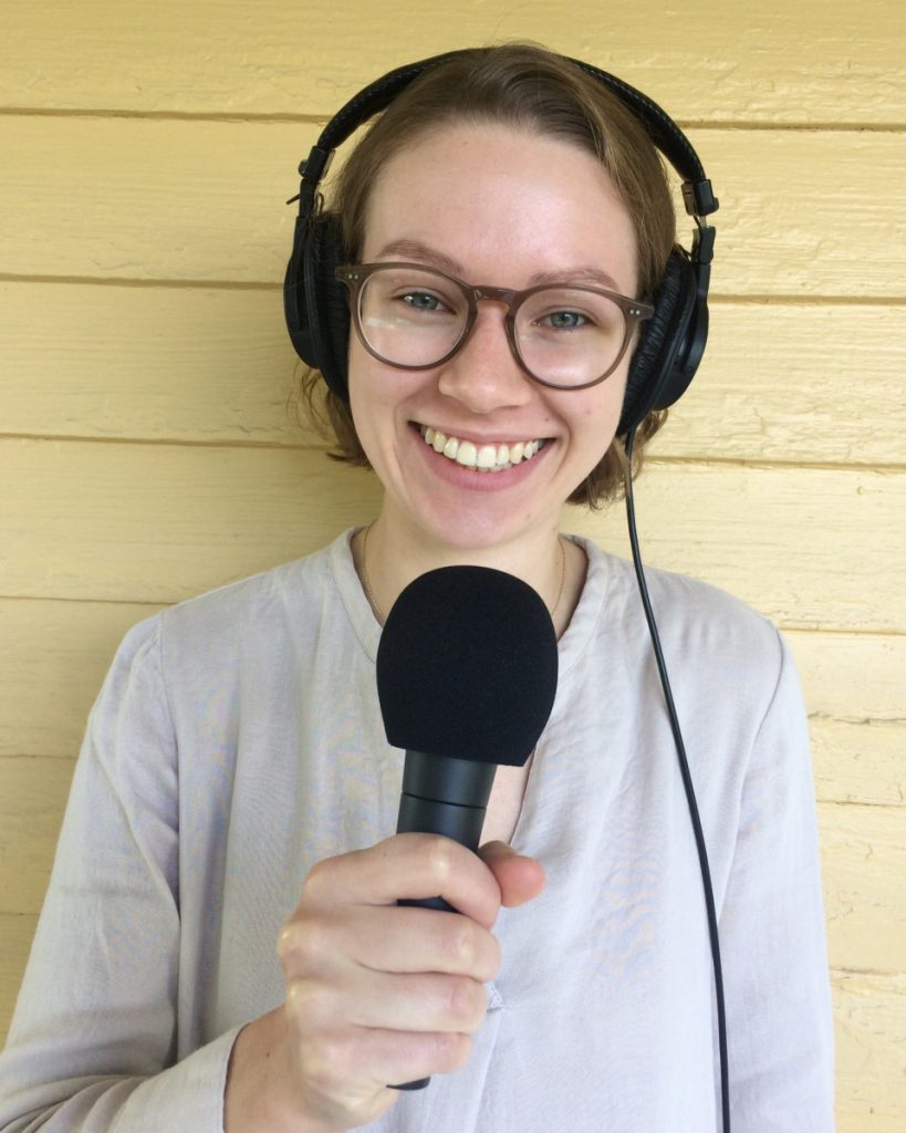 photo of Simone with microphone in front of yellow painted farmhouse type wall.